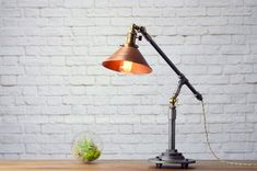 This industrial table lamp can be adjusted to control the height as well as the angle of the shade to place light where you need it most.  A 60 watt filament bulb lights up an 8 inch aged copper shade for a warm ambient glow.  The lamp is constructed from heavy duty industrial piping. The vintage bulbs are easy to replace and can be found at your local hardware store. Power is supplied by an antique style cloth covered cord. The high end antique brass socket features a vintage on/off key…