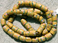 Trade Beads |  A strand of barrel shaped, small Venetian fancy beads made at the end of the 1800`s and used for the African trade. | The body of the beads is yellow and the hand painted decoration is pink, white and green.