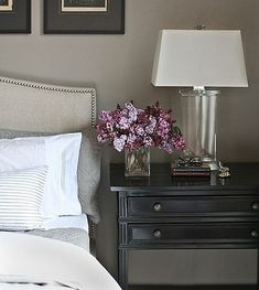 The purple pops with the grey wall color - beautiful bedroom, upholstered headboard, black nightstand...