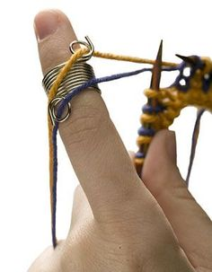 Found this nifty little gadget for sale over at KnitPicks. Would work for crochet as well.  Wire Yarn Stranding Guide -  This coiled ring is worn on the tip of your finger, to keep your yarns untangled and at an even tension while you knit a colorwork project. Whether you knit English or Continental style, this yarn stranding guide will speed up your Fair Isle and double knitting!