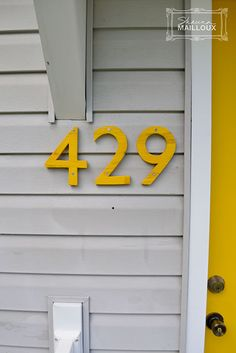 Yellow front door and plywood numbers  Gold Buttercup by Olympic Shutters are Elkhorn Cactus by Valspar