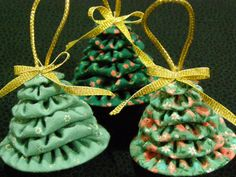 Three Christmas tree ornaments made of fabric yo yos to look like miniature Christmas trees. Each ornament consists of six yo yos, made of calico print, each one slightly smaller to stack into a tree shape. The bottom yo yo is lined with a piece of cardboard, to keep the shape intact. A small bell is glued to the bottom of the tree, and a satin ribbon bow and matching cord hanger are glued to the top of the tree.  This listing is for the set of three ornaments pictured in the photos. They…