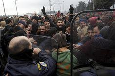Stranded migrants try to break a Greek police cordon