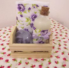 Um kit artesanal com toalha de lavabo,sabonete líquido e sabonete em barra.