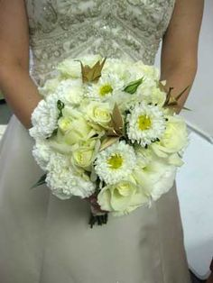 A bridal bouquet of ours featuring white lisianthus, ivory roses and white asters. The gold origami cranes used in this bouquet were provided by the bride.