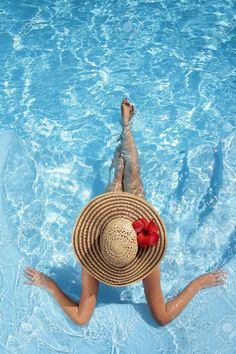 Woman sitting in a swimming pool in a large sunhat Stock Photo