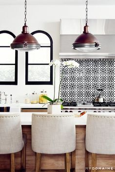 like the encaustic tile backsplash behind the cooktop, black window frames and counter seating