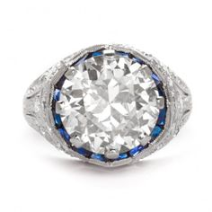 Lady's Art Deco diamond  platinum engagement ring, eaturing a center mine-cut diamond, about 4.25 cts., in a platinum filigree setting, framed with sapphires and accented with diamonds; 5.4 grams