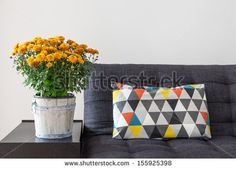 Bright cushion on a sofa, and orange chrysanthemums on a side table. by GoodMood Photo, via Shutterstock