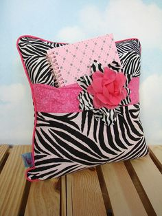 A beautiful pillow and it has a purpose!    This great pillow is perfect for a student, teen, or any girl with a tablet type device, a journal or diary. The pillow pocket makes a great stashing place for those personal items. It's a creative way to keep these things safe but handy and adds color and distinction to the room where it lives! My granddaughter keeps a current book and her reading light in hers. She always knows where her Kindle is AND it keeps it away from her younger brother and…