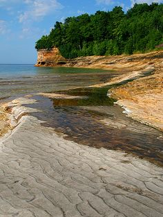 """This photograph was taken at Mosquito Beach, located in the Pictured Rocks National Lakehsore in the Upper Peninsula of Michigan. The """"Pictured Rocks"""" are the colorful cliffs, seen in the background of the photo, that make up this unique stretch of shoreline along Lake Superior."""