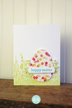 Egg-shaped polka dotted paper is hiding in the stamped and die-cut grass on this handmade Easter card. The dots on the paper look exactly like what you make with a hole puncher.