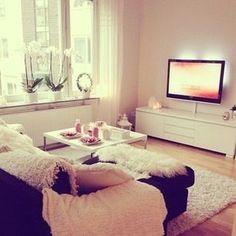 Mesa de TV. Alfombra peluda, blanca y redonda.