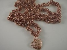 This beautifully textural chain necklace and earring set is rose gold plated. The necklace is 27-1/4 inches long and has a filigree heart pendant which hangs 3/4 inch below the chain. It closes with a rose gold plate lobster clasp. The earrings have matching filigree hearts with a light pink Swarovski bead dangle which hangs 1 inch below the rose gold plated leverbacks. By Marcia Etheridge $128.70
