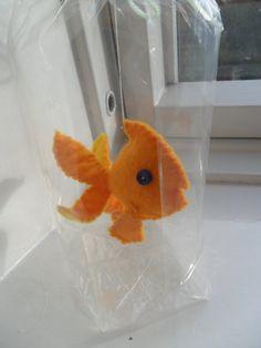 Se trata de un bonito amarillo y oro goldfish color de fieltro. Pueden sacarlo de la bolsa y le cuelgan como adorno. Él vería grande colgando de su retrovisor o árbol de Navidad! O lo deje en la bolsa como una mascota de muy bajo mantenimiento (él no moriré nunca.) No tienes que alimentarlo o llevarlo a pasear. Supongo que podría llevarlo de paseo si quería. Tiene ojos de botón azul brillante. Él haría un muy divertido regalo para alguien especial.    Cada pescado es hecho sin un patrón que…
