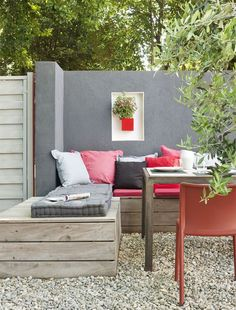 Cute colorfull pallet corner bench. Grey wall. Red. Lets go outside.