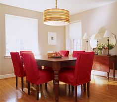Dining room with red chairs and a striped lamp - love the red slip covers and the ceiling lamp
