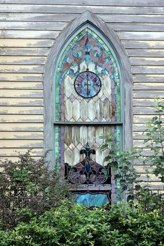An old stained glass window would make a great feature for the little house near the edge of the woods