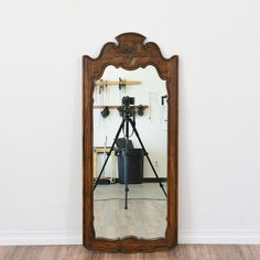 This mirror is featured in a solid wood with a rustic dark oak finish. This mirror is in great condition with curved trim and intricate carved floral designs. Unique mirror perfect for a vanity dresser! #rustic #decor #mirror #sandiegovintage #vintagefurniture