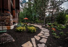 """A view of the flagstone path leading to the patio. The path connects to the patio and then starts to """"deconstruct"""" as it moves away from the patio, leading to the natural chaos of nature."""