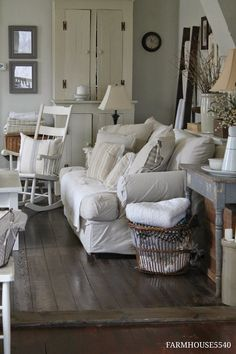 table behind couch, white rocking chair with pillow, baskets of blankets