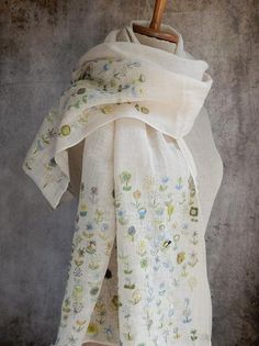 Creamy colored linen embroidered with  flowers on the hems of the scarf. About 20 x 54 inches.