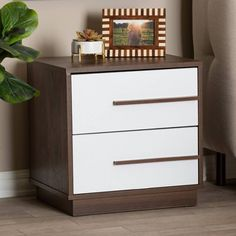 Constructed from engineered wood Two-tone white and walnut brown finish Two drawers Brown PVC plastic drawer handles Metal drawer glides Assembly required Made in Malaysia Engineered Wood, Beautiful Furniture, White Table Top, Storage Cabinets, Baxton, Wood Nightstand, Furniture Collections, Wood Finish, White Nightstand
