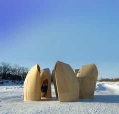 The wooden, wind-streamed cabins cluster around to form a small settlement, a prototypical village. Densely positioned, the keep the icy winds at bay. Each individual cabin is made of thin flexible plywood placed taut over an ellipsoid footprint to create a small room, with additional structural power delivered by a stable spine. The tension created in this way is then resolved by a series of deliberate cuts into the surface.