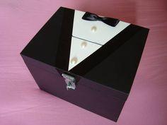 Caixa de mdf personalizada como Smoking Hora da gravata/ Corte da gravata. Decorada com fita cetim, botões de pérolas e gravata borboleta de cetim. A caixa no modelo de cofre, com dobradiça e fechadura com cadeado. Pode ser feita só com dobradiça e fecho. Pode ser usada para colocar dinheiro do corte da gravata. O prazo para confecção pode variar para mais ou para menos dependendo dos pedidos já existentes. CONSULTE DISPONIBILIDADE. R$ 45,00