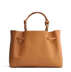 The Tote in Caramel from von Holzhausen made from natural grained soft Italian leather with painted edges. Shoulder straps elongate when worn for a comfortable fit. Features two open pockets on interior and removable signature wallet.