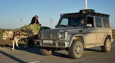 Mike Horn in a Mercedes-Benz G-Class next to a cart being pulled by a donkey.