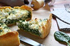 Torta salata con spinaci e feta greca con foglie di basilico e macinapepe