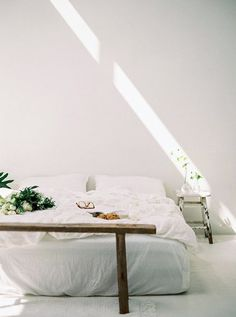 minimalist white bedroom with bed on floor and bedside stool / sfgirlbybay