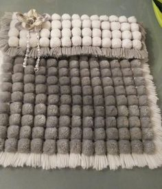 Pom pom blanket in grey and white.