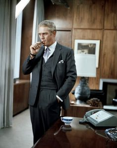Steve McQueen in a three-piece suit with a cigar.