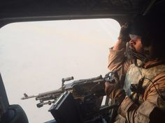 An Emirati gunner aboard a Chinook military helicopter scans the desert over Yemen on Wednesday, Sept. 16, 2015.