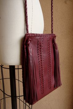 Handcrafted out of sumptuous wine deerskin. Hand woven detail. Hand braided adjustable strap with tassels. Lined in suede with inside pocket