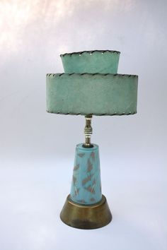 Stylish little mid century modern glass lamp with resin two-tiered whipstitched shade. Base shape echoes Yves Saint Laurent's trapeze dress of the era. Buy it in my Etsy store.