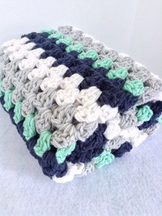 Beautiful nautical inspired crochet baby blanket for boy or girl  This gorgeous blanket is super soft and cuddly Stitched with premium soft acrylic yarn, it is machine wash cold on gentle cycle and tumble dry low- easy care for a busy new mom!  This sweet gift measures approximately 30 x 30 and is the perfect size for naptime, playmat or stroller. A nautical nursery theme will be enhanced by this navy, mint, soft grey and white blanket as a beautiful addition! Tiny sailor photo sessions…