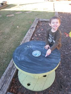 Upcycled wooden cable spool with chalk holder. So amazing – keep the chalk mess outside! I love this idea.