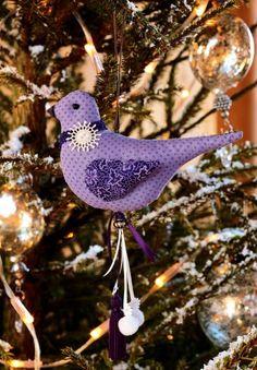 Un oiseau cousu en tissu mauve à motifs pour décorer le sapin de Noël ou une poignée de porte ou un portemanteau