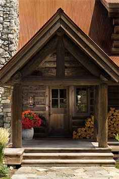 Log home entrance by PrecisionCraft Log & Timber Homes; love the splash of color with the flowers