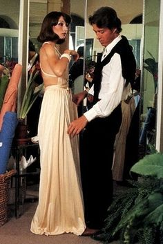 Halston fits one of his signature dresses on Anjelica Huston, 1972.