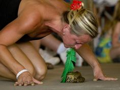 Melissa Brewer of Finchville, Ky., tries to motivate a frog during the 40th Frog Follies frog jumping competition in Evansville, Ind., on Aug. 29, 2015.   Denny Simmons/Evansville Courier & Press, AP