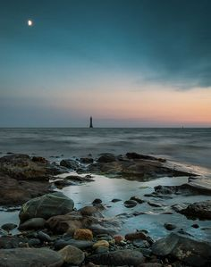 In the distance against a hazy sunset is silhouette of Haulbowline Lighthouse taken from Cranfield Beach, County Down.