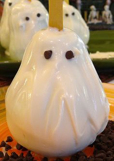 Graveyard Grub - Ghosts on a Stick - Pears dipped in white chocolate and decorated with faces.