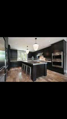 the light flooring and backsplash with the dark wood make this a really alluring kitchen