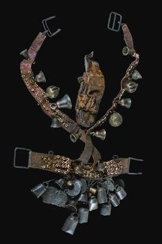 West Nepal | Magar | Sharman belt; broad waistbelt with large metal clasp, decorated with cowrie shells and various appendages along the lower rim (ten metal bells and hammered badges), supplemented by crossed straps which were worn like a pair of braces, decorated with various bells and spherical rattles, as well as multipart leather case