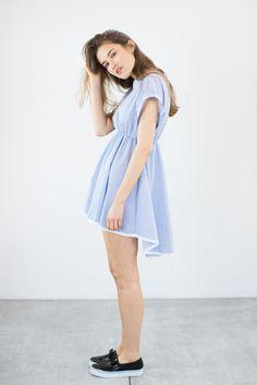 Verspieltes Kleid aus blau-weiß gestreiftem Baumwollstoff. Das Kleid ist locker geschnitten und auf Teillenhöhe mit einem Gummizug gerafft. Es ist hinten weiter geschnitten als vorne und fällt...