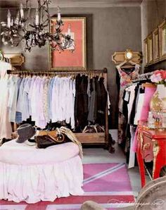 Clothes racks on rollers; skirted ottoman on rug; chandelier